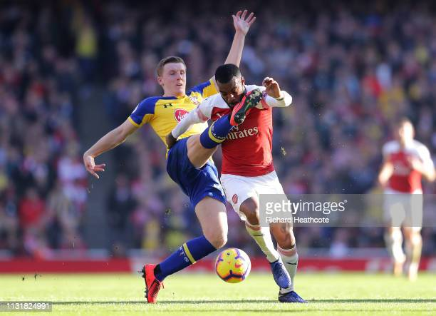 Alexandre Lacazette of Arsenal is challenged by Matt Targett of Southampton during the Premier League match between Arsenal FC and Southampton FC at...