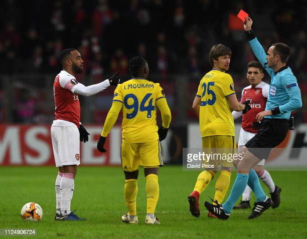 Alexandre Lacazette of Arsenal is shown the red card by referee Srdjan Jovanovic during the UEFA Europa League Round of 32 First Leg match between...