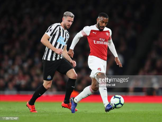 Alexandre Lacazette of Arsenal is watched by Paul Dummett of Newcastle United during the Premier League match between Arsenal FC and Newcastle United...