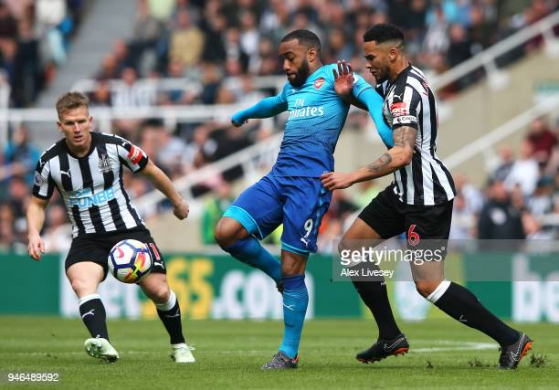 Alexandre Lacazette of Arsenal Jamaal Lascelles of Newcastle United and Matt Ritchie of Newcastle United battle for possession during the Premier...