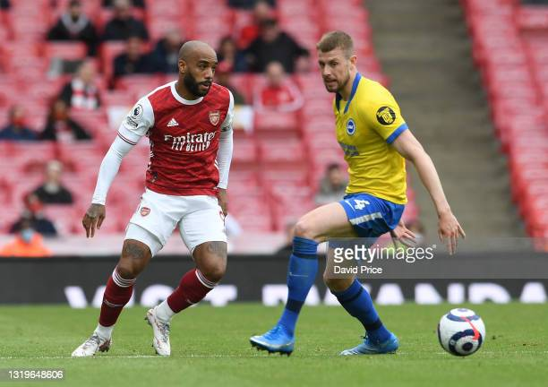 Alexandre Lacazette of Arsenal passes the ball under pressure from Adam Webster of Brighton during the Premier League match between Arsenal and...