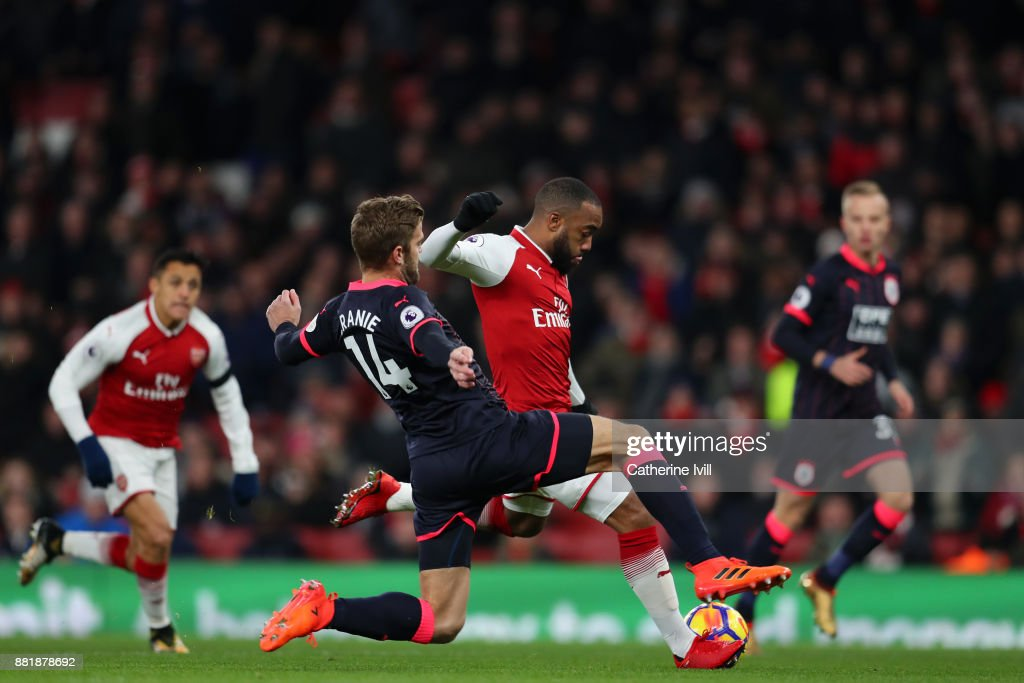Alexandre Lacazette of Arsenal scores his sides first goal past Martin Cranie of Huddersfield Town during the Premier League match between Arsenal and Huddersfield Town at Emirates Stadium on November 29, 2017 in London, England.