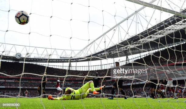 Alexandre Lacazette of Arsenal scores his side's fourth goal past Joe Hart of West Ham United during the Premier League match between Arsenal and...