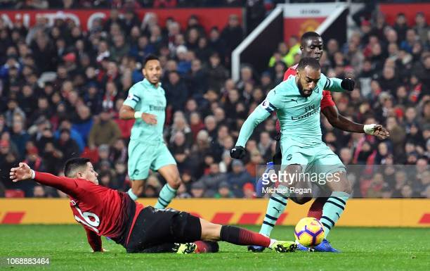 Alexandre Lacazette of Arsenal scores his team's second goal as he is challenged by Marcos Rojo of Manchester United during the Premier League match...