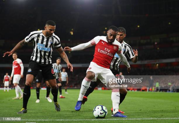 Alexandre Lacazette of Arsenal shields the ball from Jamaal Lascelles and Deandre Yedlin of Newcastle United during the Premier League match between...