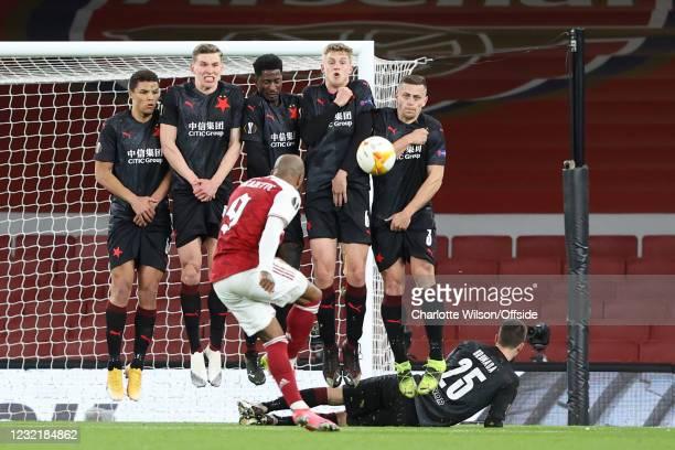 Alexandre Lacazette of Arsenal shoots against Slavia's jumping defensive wall during the UEFA Europa League Quarter Final First Leg match between...