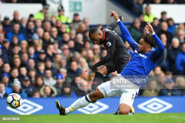 Alexandre Lacazette of Arsenal shoots as Ashley Williams of Everton attempts to block during the Premier League match between Everton and Arsenal at...