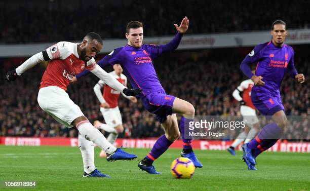 Alexandre Lacazette of Arsenal shoots past Andy Robertson of Liverpool as Virgil van Dijk of Liverpool looks on during the Premier League match...