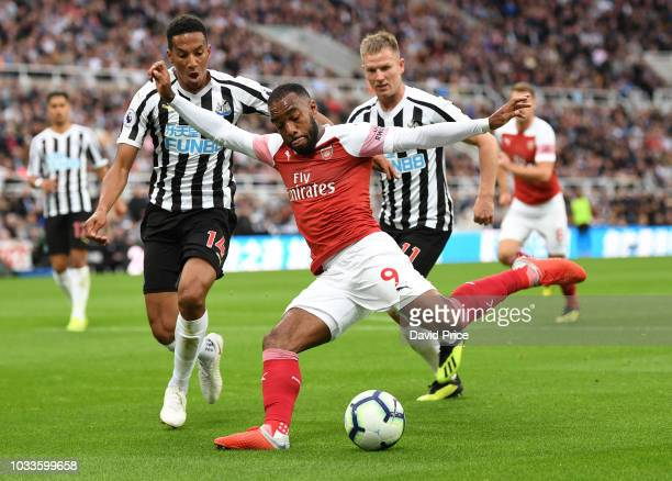 Alexandre Lacazette of Arsenal shoots under pressure from Isaac Hayden of Newcastle during the Premier League match between Newcastle United and...