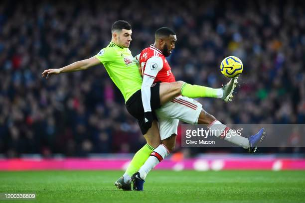 Alexandre Lacazette of Arsenal tackles with John Egan of Sheffield United during the Premier League match between Arsenal FC and Sheffield United at...