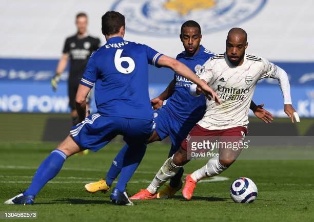 Alexandre Lacazette of Arsenal takes on Jonny Evans and Ricardo Pereira of Leicester during the Premier League match between Leicester City and...