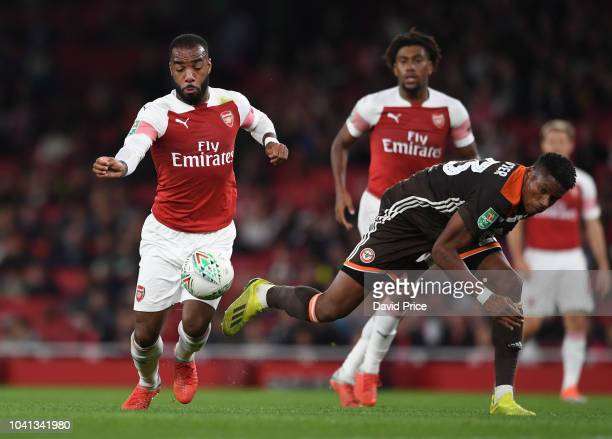 Alexandre Lacazette of Arsenal takes on Julian Jeanvier of Brentford during the Carabao Cup Third Round match between Arsenal and Brentford at...