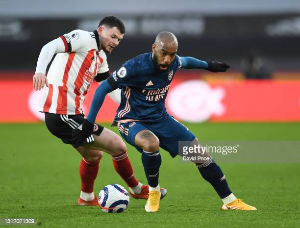 Alexandre Lacazette of Arsenal turns away from Oliver Burke of Sheffield United during the Premier League match between Sheffield United and Arsenal...