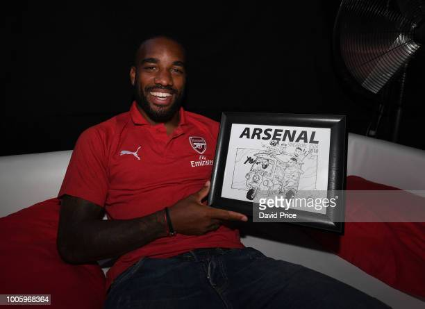Alexandre Lacazette of Arsenal with a gift from a fan after the new Arsenal Puma 3rd kit launch at Esplande Theatres on the Bay on July 27 2018 in...