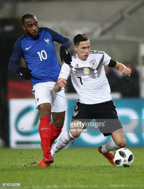 Alexandre Lacazette of France and Julian Draxler of Germany battle for possession during the international friendly match between Germany and France...