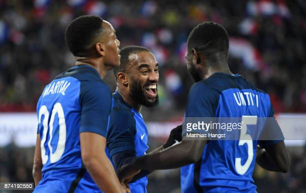 Alexandre Lacazette of France celebrates scoring his sides first goal with Anthony Martial of France and Samuel Umtiti of France during the...