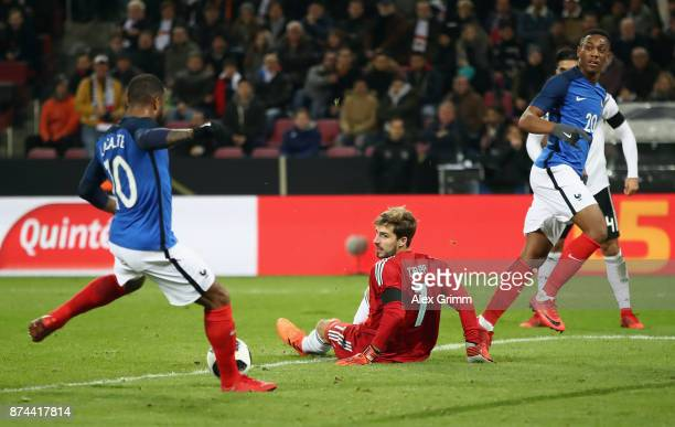 Alexandre Lacazette of France scores his team's first goal past goalkeeper Kevin Trapp of Germany during the international friendly match between...