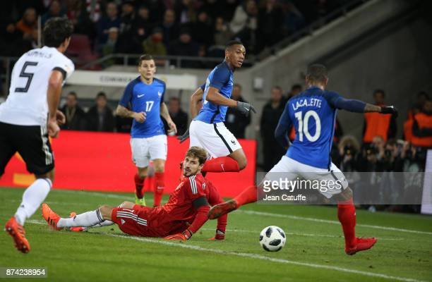 Alexandre Lacazette of France scores the first goal for France with an assist from Anthony Martial while goalkeeper of Germany Kevin Trapp looks on...