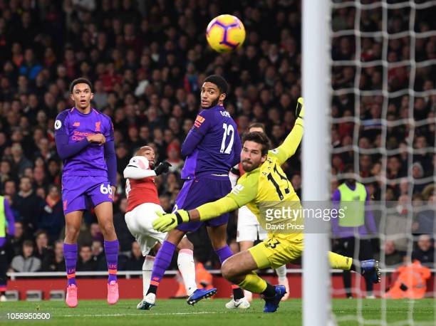 Alexandre Lacazette scores a goal for Arsenal as Alexander TrentArnold Joe Gomez and Alisson of Liverpool look on during the Premier League match...