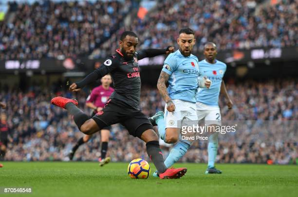 Alexandre Lacazette scores a goal for Arsenal under pressure from Nicolas Otamendi of Man City during the Premier League match between Manchester...