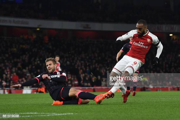 Alexandre Lacazette scores a goal for Arsenal under pressure from Martin Cranie of Huddersfield during the Premier League match between Arsenal and...