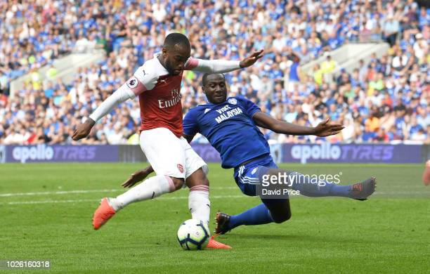 Alexandre Lacazette scores Arsenal's 3rd goal under pressure from Sol Bamba of Cardiff during the Premier League match between Cardiff City and...