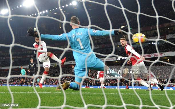 Alexandre Lacazette scores Arsenal's goal past David De Gea of Man Utd during the Premier League match between Arsenal and Manchester United at...