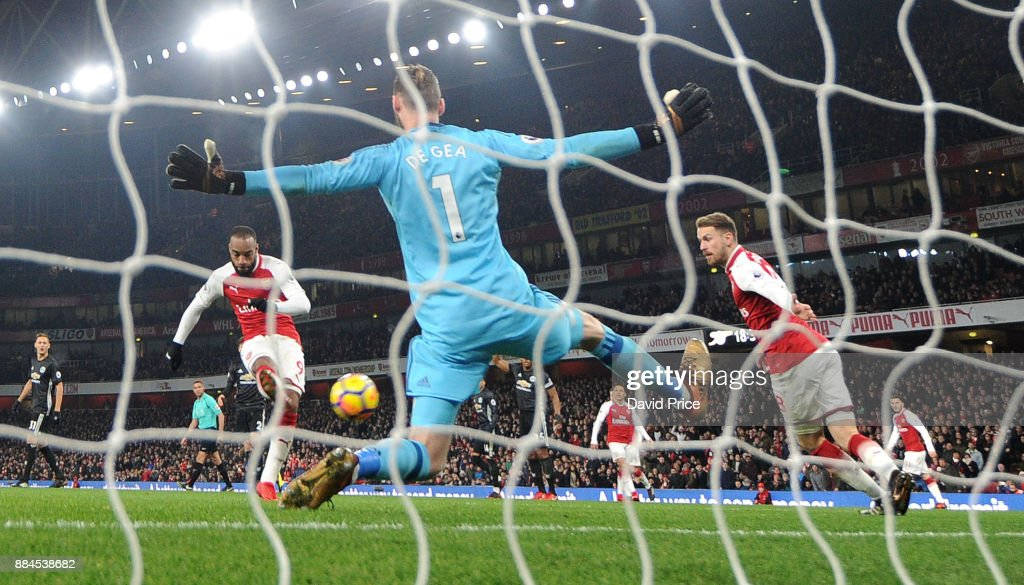 Alexandre Lacazette scores Arsenal's goal past David De Gea of Man Utd during the Premier League match between Arsenal and Manchester United at Emirates Stadium on December 2, 2017 in London, England.