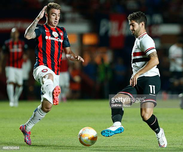 Alexandre Pato of Sao Paulo struggles for the ball with Julio Buffarini of San Lorenzo during a match between San Lorenzo and Sao Paulo as part of...