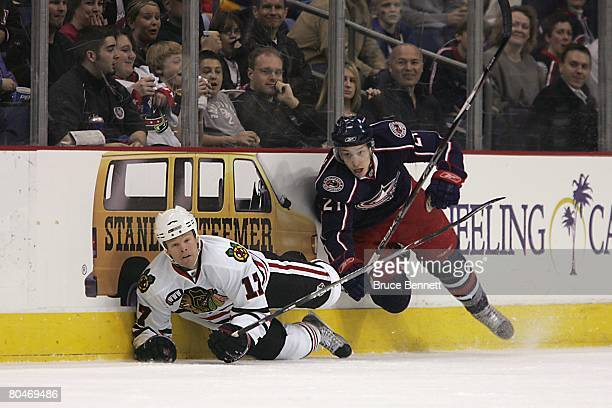 Alexandre Picard of the Columbus Blue Jackets skates on the ice while Kevyn Adams of the Chicago Blackhawks falls down on the ice during the NHL game...