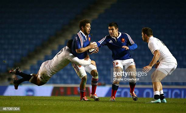 Alexandre Pilati of France looks to hold off the tackle from Joe Marchant of England during the Under 20 Six Nations Championship match between...