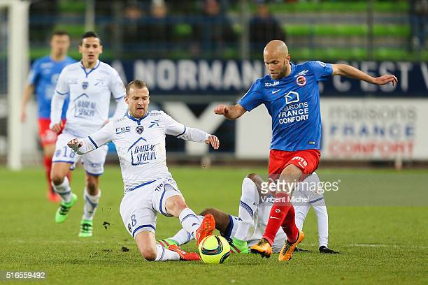 Alexandre Raineau of Caen is tackled by Stephane Darbion of Troyes during the French Ligue 1 match between SM Caen and ESTAC Troyes at Stade Michel...