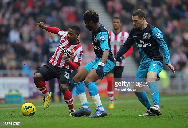 Alexandre Song and Thomas Vermaelen of Arsenal in action with Stephane Sessegnon of Sunderland during the Barclays Premier League match between...