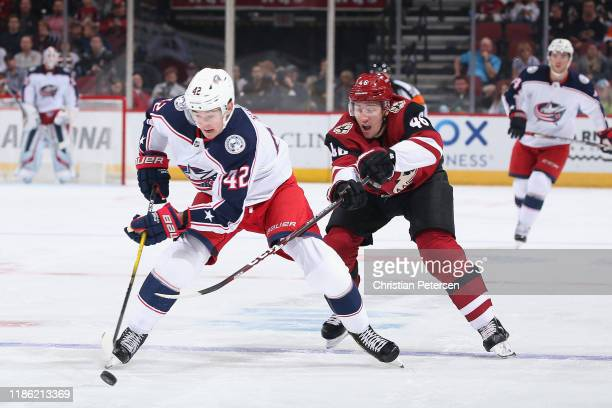 Alexandre Texier of the Columbus Blue Jackets skates with the puck ahead of Ilya Lyubushkin of the Arizona Coyotes during the first period of the NHL...