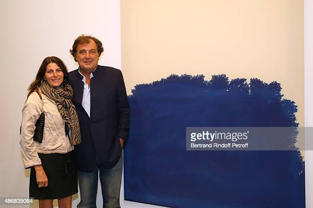Alexandre Vilgrain and his wife Denise Vilgrain pose in front of a Latifa Echakhch's Work during the 'Heroes Exhibition' to Benefit Imagine...