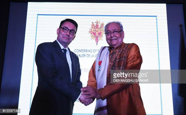 Alexandre Ziegler shakes hands after awarding the order of 'Chevalier de la Légion d'Honneur' to Indian actor Soumitra Chatterjee during a special...