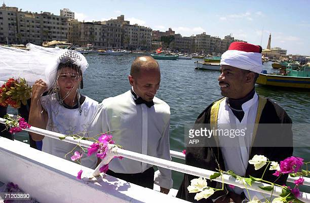 An Egyptian cleric walks ahead of Egyptian groom Mahmud Zeidan and his French bride Celine Modelon before the start of their underwater wedding...
