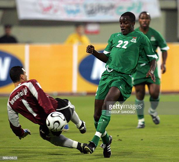 Zambian player James Chamanga scores a goal against Tunisia after passing Tunisian goalkeeper Ali Boumnijel during their Group C African Nations Cup...