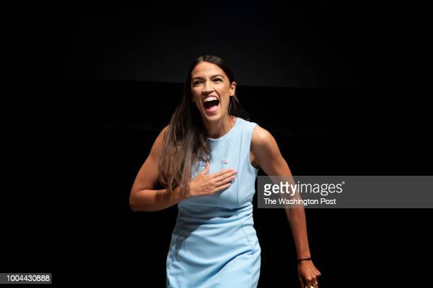 Alexandria OcasioCortez reacts as she walks onto the stage at a campaign rally in Wichita Kansas on July 20 2018 Bernie Sanders held a rally with...