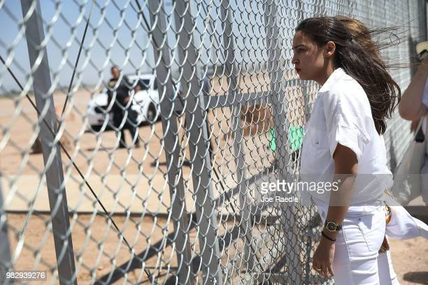 Alexandria OcasioCortez stands at the TornilloGuadalupe port of entry gate on June 24 2018 in Tornillo Texas She is part of a group protesting the...