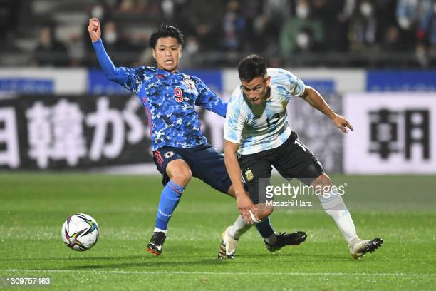 Alexandro Bernabei of Argentina and Ryotaro Meshino of Japan compete for the ball during the U-24 international friendly match between Japan and...