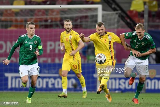Alexandru Cretu of Romania in action against George Saville and Steven Davis of Northern Ireland during UEFA Nations League 2021 match between...