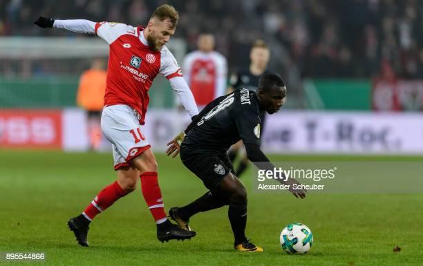 Alexandru Maxim of Mainz challenges Chadrac Akolo of Stuttgart during the DFB Cup match between 1 FSV Mainz 05 and VfB Stuttgart at Opel Arena on...