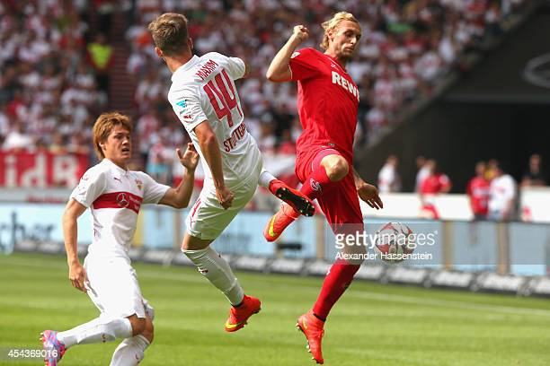 Alexandru Maxim of Stuttgart and his team mate Gotoku Sakai battle for the ball with Miso Brecko of Koeln during the Bundesliga match between VfB...
