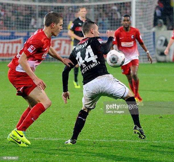 Alexandru Maxim of Stuttgart is challenged by Matthias Ginter of Freiburg during the Bundesliga match between SC Freiburg and VfB Stuttgart at MAGE...