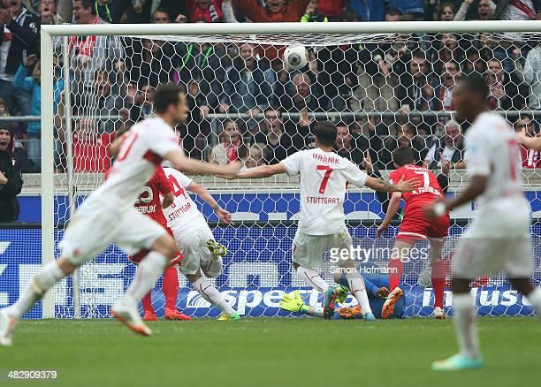 Alexandru Maxim of Stuttgart scores his team's first goal against goalkeeper Oliver Baumann of Freiburg during the Bundesliga match between VfB...