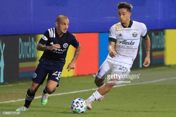 Alexandru Mitrita of New York City fights for the ball with Pablo Bonilla of Portland Timbers during a quarter final match of MLS Is Back Tournament...
