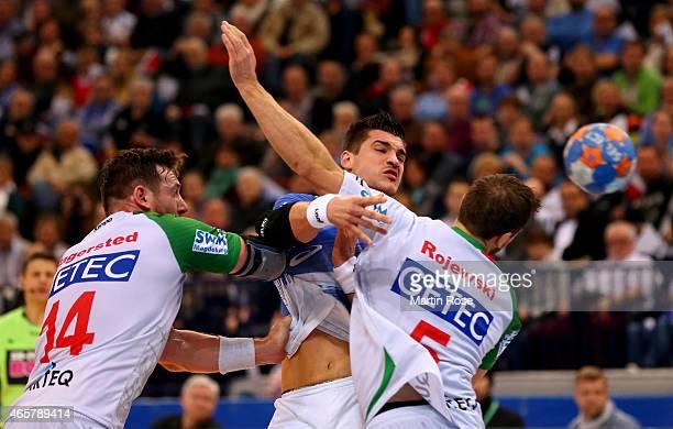 Alexandru Simicu of Hamburg challenges Jacob Bagersted and Andreas Rojewski of Magdeburg during the DKB Bundesliga handball match between HSV...