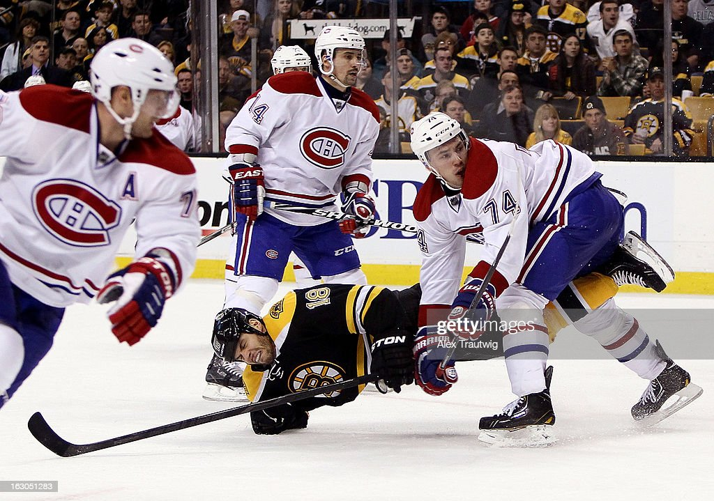 Alexei Emelin #74 of the Montreal Canadiens checks Nathan Horton #18 of the Boston Bruins during a game at the TD Garden on March 3, 2013 in Boston, Massachusetts.