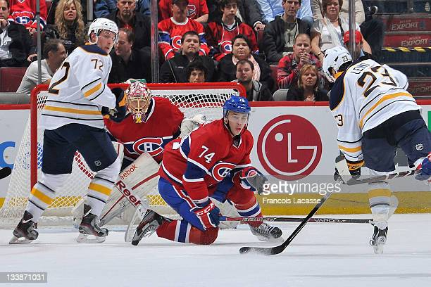 Alexei Emelin of the Montreal Canadiens goes down on his knee to block a shot by Ville Leino of the Buffalo Sabres as Luke Adam and goaltender Carey...